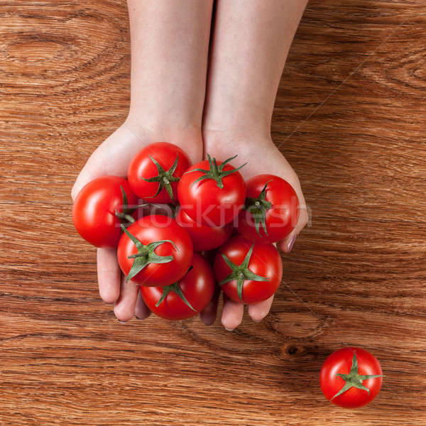 red tomatoes in hands on wood Stock photo © artjazz
