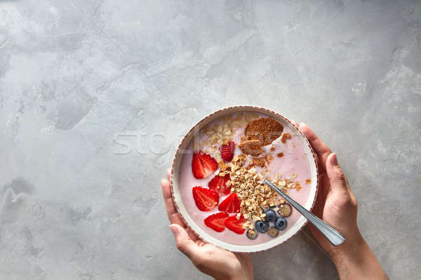 yoghurt with almond flakes, oatmeal and fresh berry served in bowl in female hands on a concrete bac Stock photo © artjazz