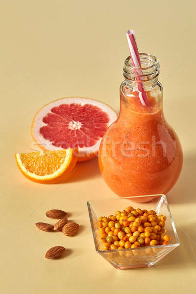 Orange citrus drink with sea buckthorn and almonds in a glass on an orange paper background Stock photo © artjazz
