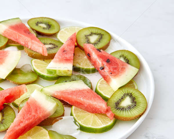 Pattern of pieces of watermelon, kiwi, lime and melting ice cubes in a plate on a gray marble backgr Stock photo © artjazz