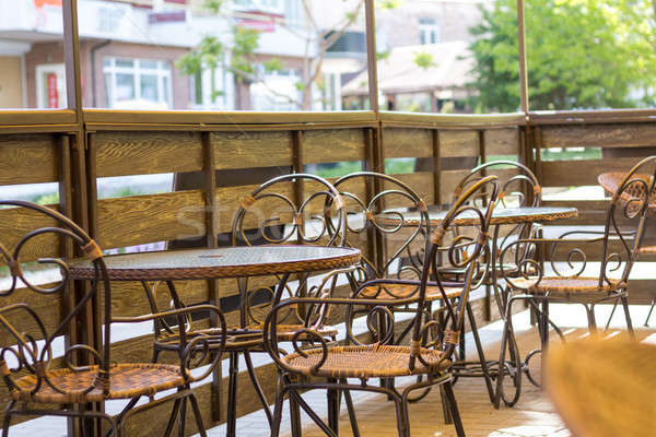Cosy terrace of the summer cafe with wicker tables and chairs Stock photo © artsvitlyna
