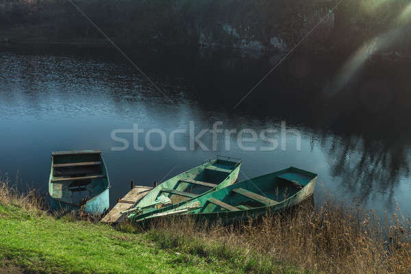 Stock photo: Three wooden boats peacefully resting on an autumn river at the