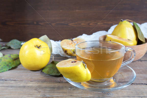 Stock photo: Cup of hot  tea and fresh quince fruit on table