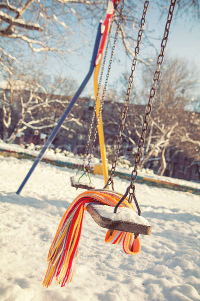 Stock photo: Empty swing with snow and checkered scarf