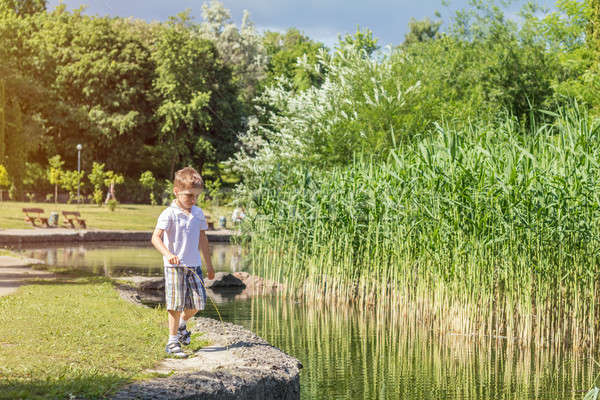 Stock photo: Happy little boy playing at the pond in the city park on a summe