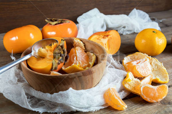 Stock photo: Fresh persimmons and tangerines fruits in bowl