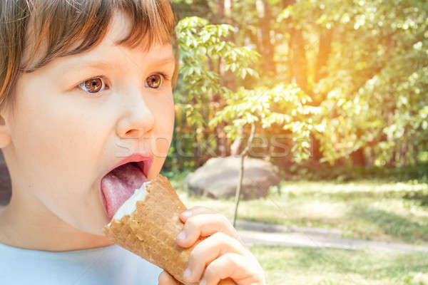 Cute little girl eating ice-cream in the city park on a summer s Stock photo © artsvitlyna