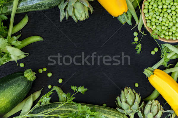 Fresh organic green vegetables on black stone floor Stock photo © artsvitlyna