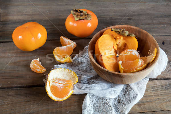 Fresh persimmons and tangerines fruits in bowl Stock photo © artsvitlyna