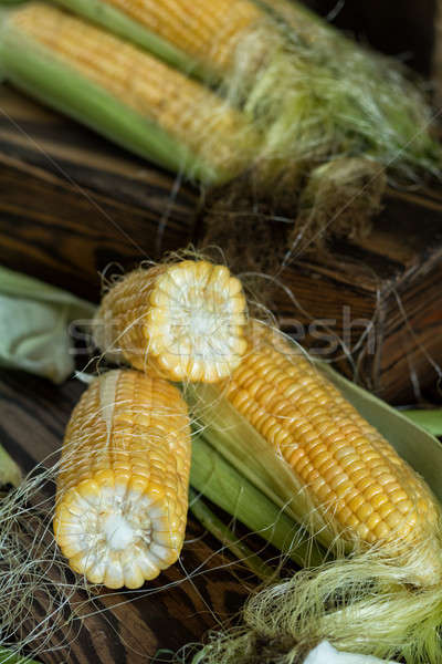 Fresh sweet corn on cobs on rustic wooden table, close up. Toned Stock photo © artsvitlyna