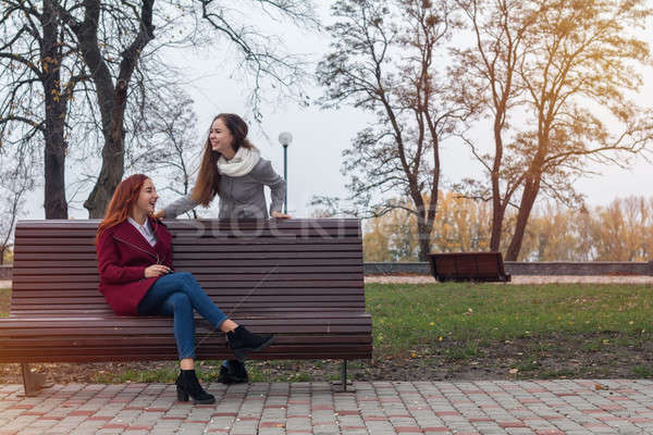 Female teenagers listening to music on smartphone at the bench i Stock photo © artsvitlyna