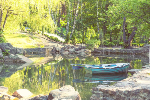 Blue wooden boat in the park pond on a sunny day Stock photo © artsvitlyna
