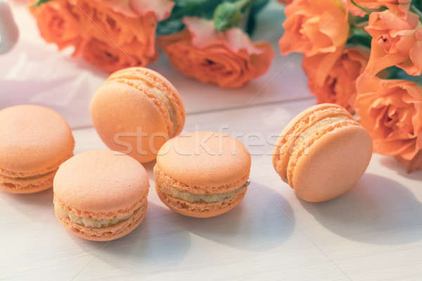 Orange macaroons and fresh little roses Stock photo © artsvitlyna