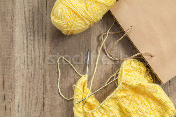 Stock photo: Light yellow knitting wool and knitting needles on wooden backgr