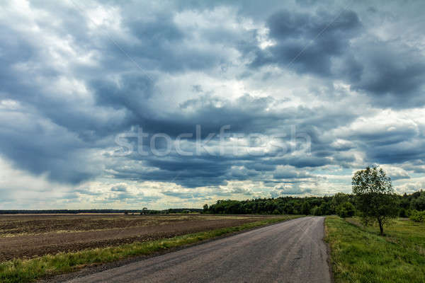 Mysterious clouds in the sky over an country road Stock photo © artsvitlyna