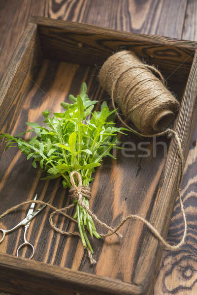 Top view of the bunch of fresh arugula in a wooden box. Dark woo Stock photo © artsvitlyna