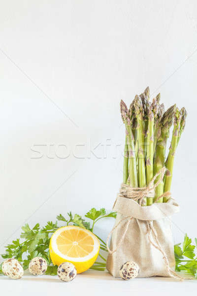 Fresh vegetables and asparagus in a little sack Stock photo © artsvitlyna
