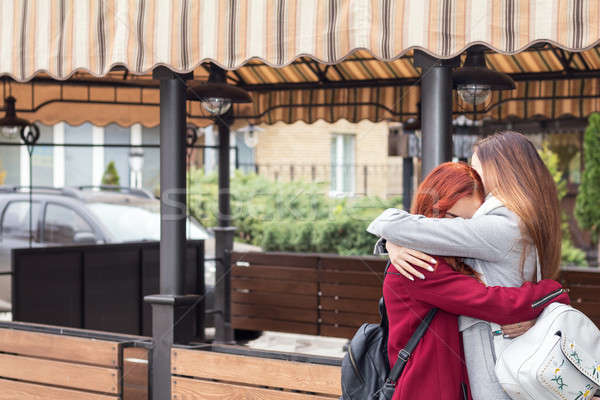 Stock photo: Two female teenagers embracing at the city street cafe