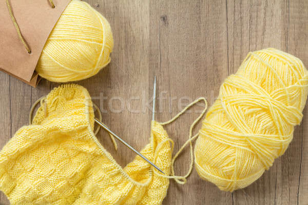 Light yellow knitting wool and knitting needles on wooden backgr Stock photo © artsvitlyna