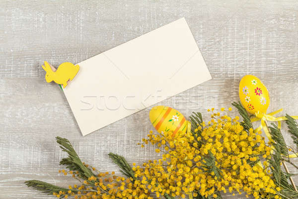 Stock photo: Easter accessories, mimosa and yellow daffodils on a light woode