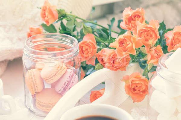 Orange macaroons, cup of coffee and fresh roses Stock photo © artsvitlyna