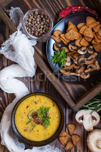 Pea soup with mushrooms in black plate. Stock photo © artsvitlyna