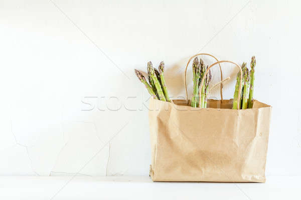 Bunches of fresh asparagus in a paper bag on white cracked wall  Stock photo © artsvitlyna