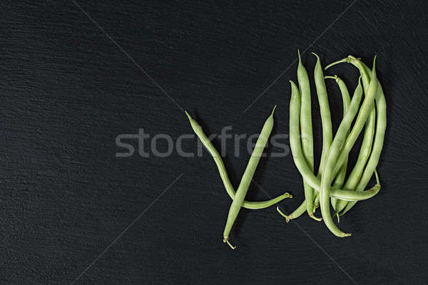 Pods fresh green beans on a black stone surface.  Top view, copy Stock photo © artsvitlyna