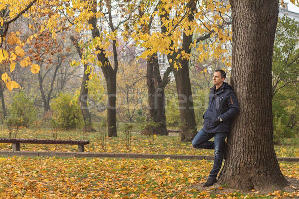 Stock photo: Handsome man walking in the autumn park