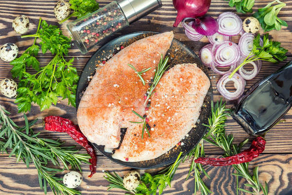 Raw uncooked chicken fillet on a cutting table Stock photo © artsvitlyna