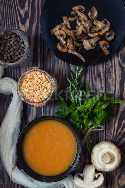 Stock photo: Pea soup and fried mushrooms in black plates