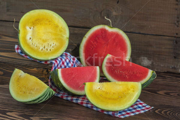 Cut red and yellow watermelons on a wooden box in a vintage wood Stock photo © artsvitlyna