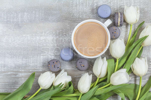 Cup of coffee, white tulips and gray macaroons on light wooden s Stock photo © artsvitlyna