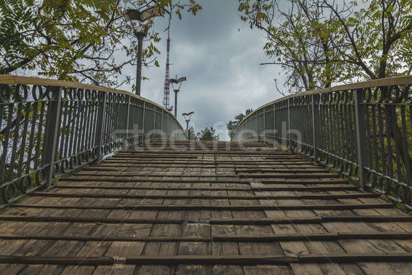 Wooden bridge on cloudy sky background Stock photo © artsvitlyna