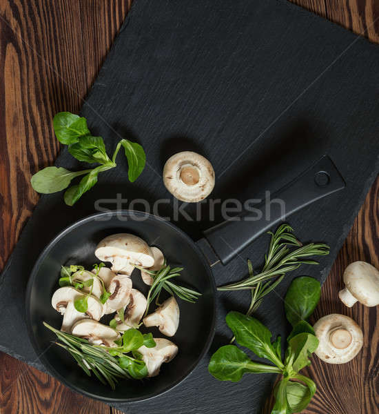 Stock photo: Top view of fresh mushrooms with mash salad and rosemary on a da