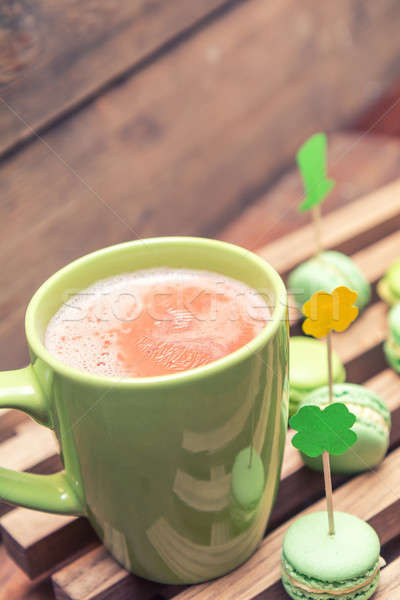 Hot cocoa in green cup and green macaroon cookies scattered on t Stock photo © artsvitlyna