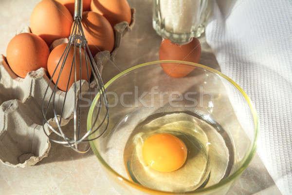 Broken egg in a glass bowl ready for whipping. Fresh chicken egg Stock photo © artsvitlyna
