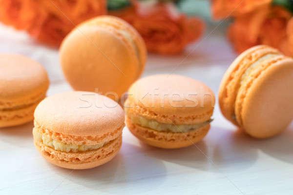 Orange macaroons and fresh little roses Stock photo © artsvitlyna