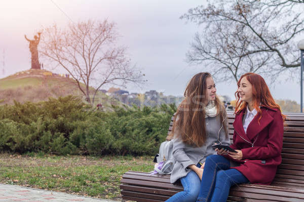 Stock photo:  Female teenagers listening to music on smartphone sitting on th