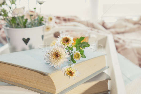 Stock photo: Chrysanthemum flowers lay on the book which is laying on the tab