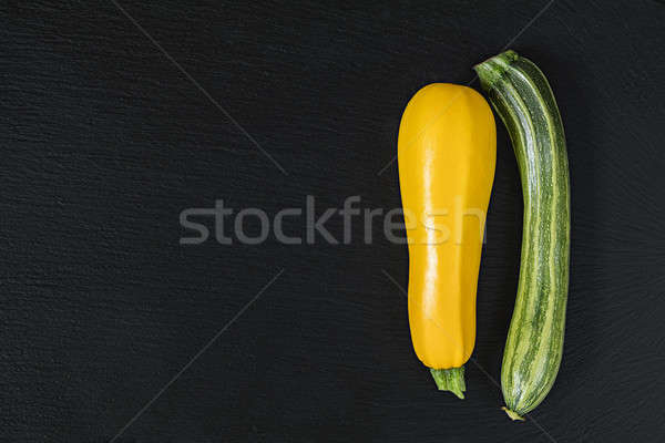 Stock photo: Striped fresh green zucchini and yellow zucchini on a black ston