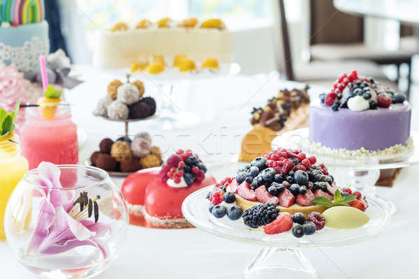 Many sweet pastries on white table with fresh summer berries. Fe Stock photo © artsvitlyna