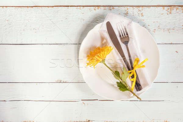 White empty plate, yellow chrysanthemum flowers, napkin, fork an Stock photo © artsvitlyna