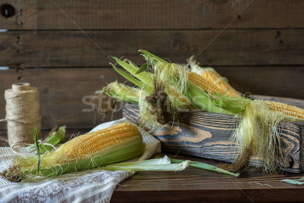 Fresh sweet corn on cobs on rustic wooden table Stock photo © artsvitlyna