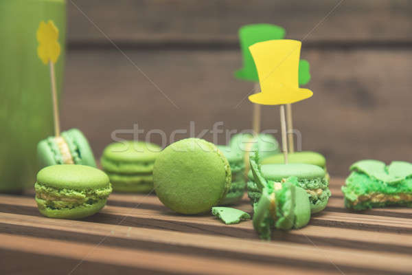 Green macaroon cookies scattered on the wooden surface with St.  Stock photo © artsvitlyna