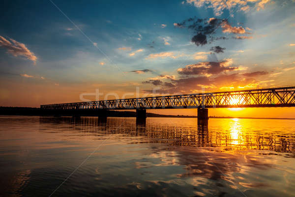 Stunning sunset colors over river with bridge in a summer evenin Stock photo © artsvitlyna
