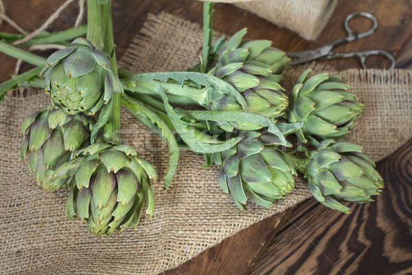 Stock photo: Two artichoke bouquets on sackcloth on wooden background. Top vi