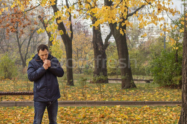 Stock photo: Handsome man walking in the autumn park. Man smoking cigarette i
