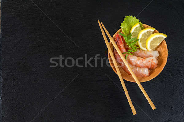 Stock photo: Shrimp on a wooden plate with wooden chopsticks