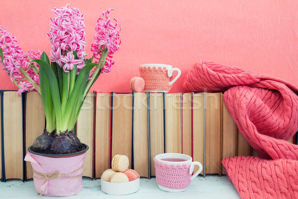 Stock photo: Pink hyacinths, macaroons, tea cups and scarf near pile of books